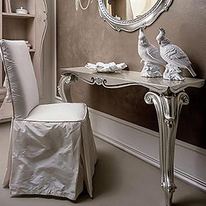 _Lord console table with metal top, champagne silver leaf finish, cat. C</br> _Castellana chair in wood upholstered in Splendore/107 fabric, cat. B</br> _Elvis mirror in wood, champagne silver leaf finish, cat. C</br> _Avril wall lamp in metal, dove grey silver leaf finish, cat. C, lampshade in pleated Ponge/01 fabric, cat. A, with pearls