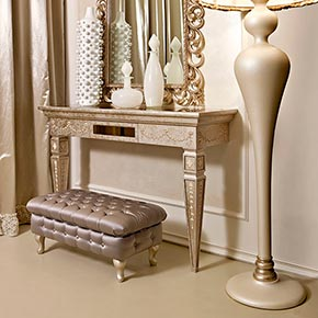 _Epoque console table in dove grey silver leaf finish, cat. C, with bronze mirror glass top and Windsor decoration</br> _Pitti mirror in wood, dove grey silver leaf finish, cat. C</br> _Operà floor lamp in wood, Cameo finish, cat. B, with fabric lampshade, cat. B, and marabou</br> _Nouvelle tufted pouffe with wooden frame upholstered in Luce fabric, cat. B, feet in Cameo finish, cat. B
