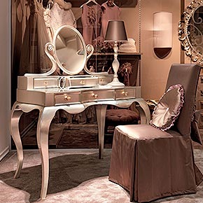 _Rimmel dressing table in wood, champagne silver leaf finish cat.C, Ballon metal handles, clear mirror</br> _Lady table lamp in wood, Cameo finish cat.B, lampshade in Rio/6074 fabric, cat.A</br> _Castellana chair upholstery in Rio/6074 fabric, cat.A