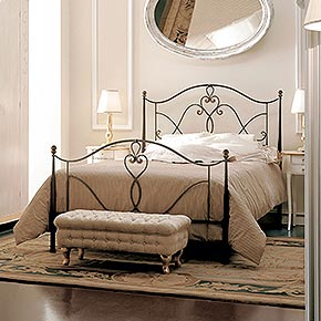 _Hand-forged iron bed rust finish, cat. B</br> _Quilt interior</br> _Sogno sheet set</br> _Ovalino wooden night tables with Bijou metal handle,ivory Tudor finish with gold details, cat. B</br> _Mezzaluna wooden chest of drawers with Torcello metal handle, ivory Tudor finish with gold details, cat. B</br> _Rina wooden table lamp, gold leaf finish, cat. C, with lampshade in Thea/07 fabric, cat. A</br> _Orlando wooden mirror, worn ivory finish, cat. B</br> _Vienna wooden mirror, antique gold leaf finish, cat. C</br> _Blasone 2-door wooden wardrobe, ivory Tudor finish with gold details, cat. B</br> _Buttoned rectangular pouffe