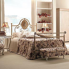 _Hand-forged iron bed ceramic-coated ivory finish, cat. B</br> _Handkerchief bedspread in fabric, cat. B</br> _Sogno sheet set</br> _Bolsters with tassels in Nevada fabric, cat. A</br> _70x70 cm cushion in Aurora/04 fabric, cat. B</br> _Karol wooden night tables with Battente metal handle,ivory crackle finish, cat. B</br> _Rina wooden table lamp, antique ivory polychrome finish, cat. D, Rosmery lampshade</br> _Orlando wooden mirror, worn ivory finish, cat. B</br> _Blasone 2-door wooden wardrobe, ivory Tudor finish with gold details, cat. B</br> _Barone wooden armchair, worn ivory finish, cat. B</br> _Buttoned rectangular pouffe