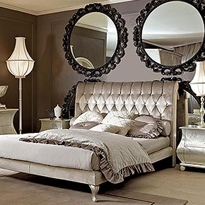_Button-tufted bed upholstered in Softmarble 3053/31, and Softmarble 3053/28 headboard center panel, cat. B</br> _Epoque table in wood, cameo finish, cat. B, base in dove grey silver leaf finish, cat. C, inserts of bronze mirror glass</br> _Epoque wooden wardrobe with 2 sliding doors, frame in cameo finish, cat. B, handles in dove grey silver leaf finish, cat. C, with tassels and bronze mirror glass</br> _Wood panelling in niger finish, cat. A, with rose and glitter decoration</br> _Rina table lamp in wood, cameo finish, cat. B, lampshade in ponge/01 fabric, cat. A</br> _Operà floor lamp in wood, cameo finish, cat. B, fabric, cat. B, with roses and pearls</br> _Bedding set (see sample book for fabrics)