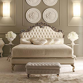 _Carved wooden bed in rose oxidized silver leaf finish, cat. C with deep buttoned headboard and bed surround upholstered with ivory leather</br> _Padded bedspread in fabric</br> _Pair of roll pillows in Nevada fabric, cat. A with matching tassels</br> _Ø50 cm cushions with button in Thea/07 fabric, cat. A</br> _Ø50 cm cushions with button in Velvet/57 fabric, cat. C</br> _Ginevra wooden tables in rose oxidized silver leaf finish, cat. C</br> _75x40 cm Regina deep buttoned pouffe in ivory leather, wooden feet in rose oxidized silver leaf finish, cat. C</br> _Alì sconce with pleated lampshade in Caravaggio Ivory fabric, cat. D</br> _Operà wooden table lamp in snow finish, cat. B, lampshade in Pongé 5 fabric, cat. A</br> _Operà 5 light floor lamp in wood and metal, snow finish cat. B, lampshades in Pongé 5 fabric, cat. A trimmed with Swarovski crystals</br> _Wall wardrobe with coplanar doors in champagne silver leaf finish, cat. C with roses and glitter decoration, and tassels 30355/02